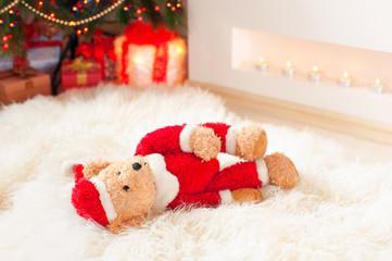 Santa tedyy bear toy lie on sheepskin near illuminated christmas