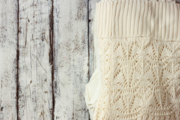 top view image of white cozy knitted sweater on a wooden table.
