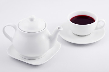 white tea cup with red tea and white teapot on white background