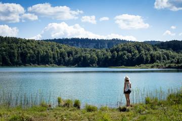 jeune fille avec un chapeau de dos au bord d'un lac en été