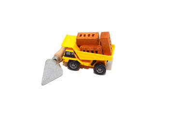 truck with bricks at a construction site. toy car with a body full of toy bricks. trowel tool blocks the path of the truck. Isolated on white background