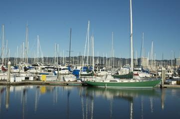 Green boat docked at marina on a clear sunny day
