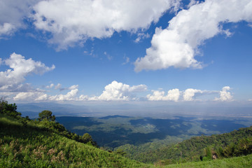 View of grass, mountain, and cloudy blue sky in Chiangmai city Thailand