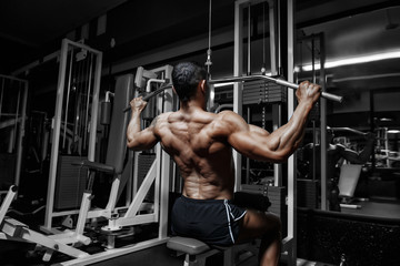 Athlete muscular bodybuilder training back workout in the gym  Wall mural