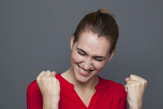 winning behavior concept - energetic 20s girl laughing and gesturing for ecstatic achievement and success,studio shot on gray background