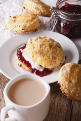 English pastries: scones with jam and tea with milk close-up. vertical