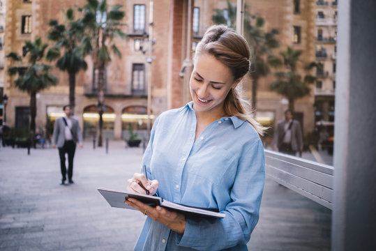 Attractive young businesswoman writting in notebook