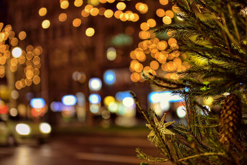 Branch of decorated Christmas tree in late evening on the street with night illumination