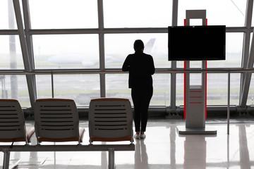 Woman standing near window in airport terminal