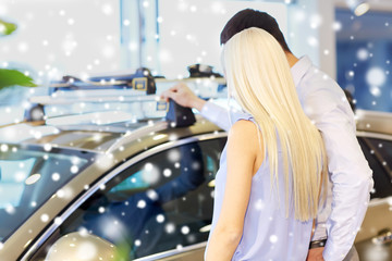couple choosing car in auto show or salon
