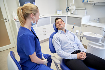 happy female dentist with man patient at clinic