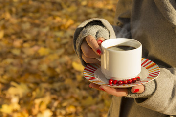 Female holding a cup of coffee outdoors