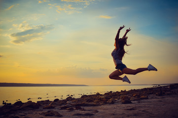 Image of beautiful young lady having fun jumping high over open water on summer outdoors background copy space