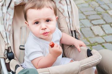 Kind im Kinderwagen ißt eine Wurst