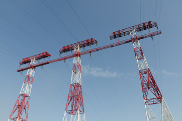 supports of high-voltage power lines against the blue sky