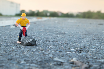 small figure of a man digging street
