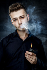 Elegant young handsome man with a cigarette and a lighter. Studio fashion portrait.