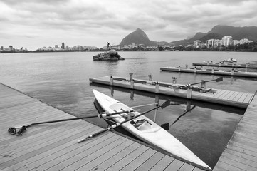 Rowing boat with oars docked at a wood pier on the Lagoa Rodrigo de Freitas lagoon with a view of of the Rio de Janeiro Brazil skyline
