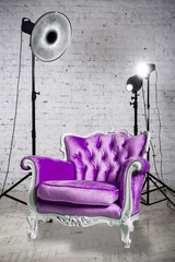 Photographic studio with equipment, accessories and violet armchair