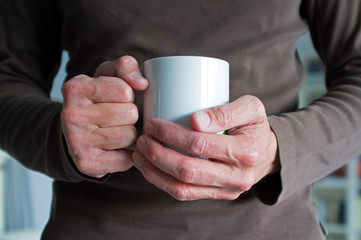Two male hands holding a cup of coffe or tea