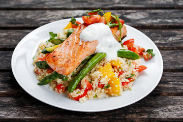 Pan fried Salmon with tender asparagus, courgette served on couscous mixed with sweet tomato, yellow pepper, with greek yogurt on old wooden table.