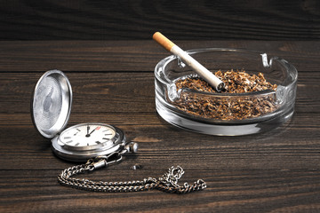 Vintage pocket watch and a cigarette with a glass ashtray on the old wooden table