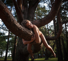 Naked woman lying on a tree branch