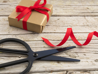 black scissor, gold gift and red ribbon on wooden background