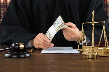 Corrupt Judge Holding Dollar Bundle At Desk