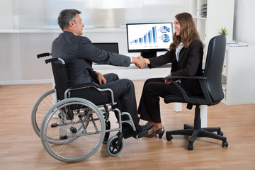 Businesswoman Shaking Hands With Disabled Businessman