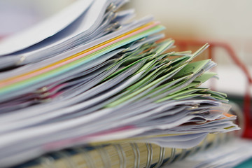 Pile of documents and notebook in red basket