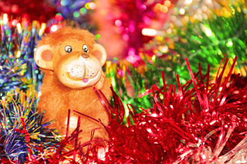 Festive colorful background with Christmas tinsel and fire monkey