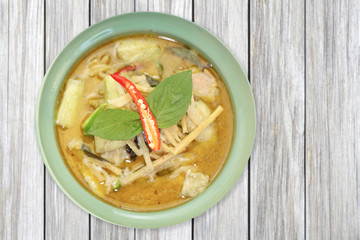 Green curry chicken with vegetable on wood table