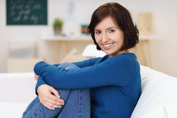 lächelnde frau sitzt auf dem sofa und umfasst die knie mit den armen