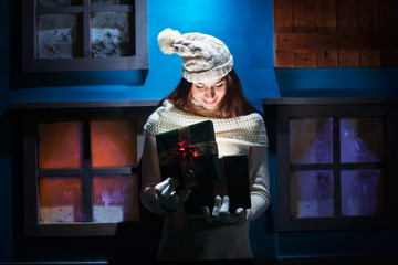 young woman opens her gift Christmas in a magical and colorful h