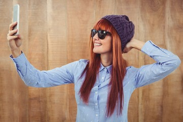 Smiling hipster woman taking selfie