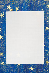 Blank sheet of paper on Christmas blue background with golden stars and glitter