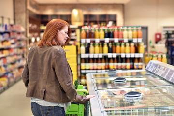 Frau beim Einkauf im supermarkt an einer Kühltheke // woman buys in the supermarket - looking into a freezer