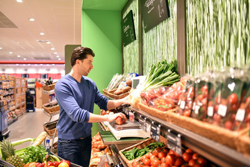Mann wiegt Obst im Supermarkt ab // 