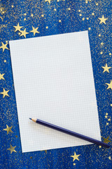 Blank sheet of paper  and blue pencil on Christmas blue background with golden stars and glitter