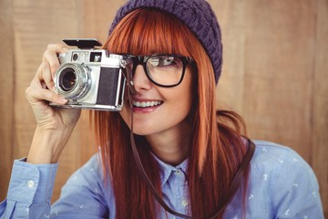 Smiling hipster woman taking pictures with a retro camera