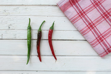 Fresh chilly peppers on white wooden table and plaid table cloth