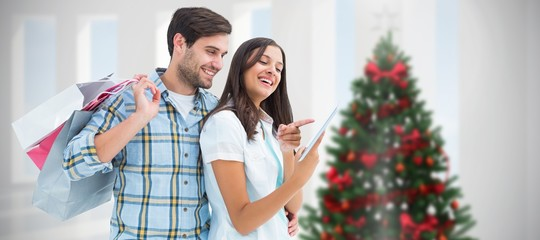 Composite image of happy couple with shopping bags and tablet