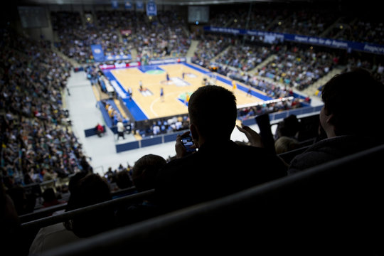 Silhouettes of fans at professional basketball game.