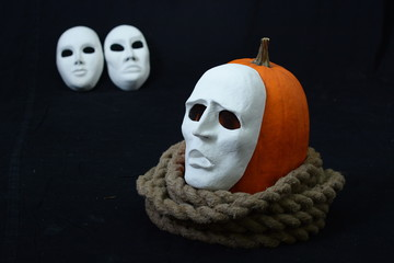 white theatrical mask with pumpkin and rope