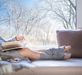 Young beautiful brunette woman with cup of coffee and gingerbread wearing knitted cardigan sitting home relaxing by the window. Snowy winter home chill out concept.