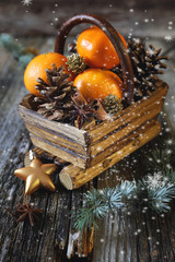 Christmas basket with tangerines, cinnamon sticks and pine cones