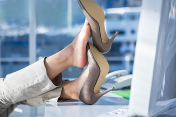 Businesswoman with her legs on her desk