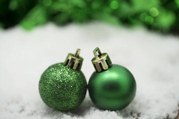 Green Christmas balls on snow against green bokeh background