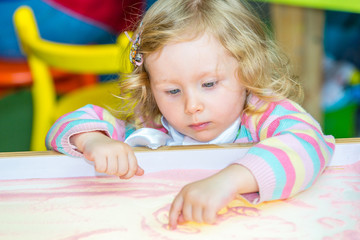 Cute child girl drawing draws developing sand in preschool at table in kindergarten by method of Montessori